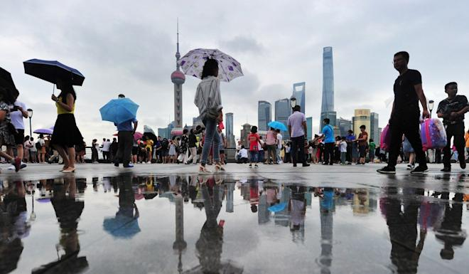 People walk on the bund near the financial district of Pudong in Shanghai. Photo: Reuters