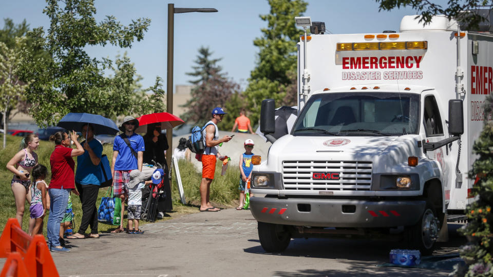 CORRECTS DATE TO WEDNESDAY, JUNE 30, 2021, INSTEAD OF TUESDAY, JUNE 29 FOR PHOTOS: JMC101-111, 113 A Salvation Army EMS vehicle is setup as a cooling station as people lineup to get into a splash park while trying to beat the heat in Calgary, Alberta., Wednesday, June 30, 2021. Environment Canada warns the torrid heat wave that has settled over much of Western Canada won't lift for days. (Jeff McIntosh/The Canadian Press via AP)
