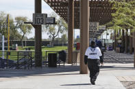 A security guard, walks through an empty American Family Fields, the spring training home of the Milwaukee Brewers, in Phoenix, Sunday, March 15, 2020. The remainder of spring training baseball games have been canceled due to the coronavirus. (AP Photo/Sue Ogrocki)