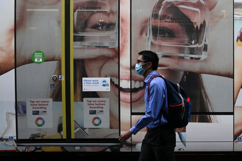 A person wearing a protective face mask walks past a tram in Sydney