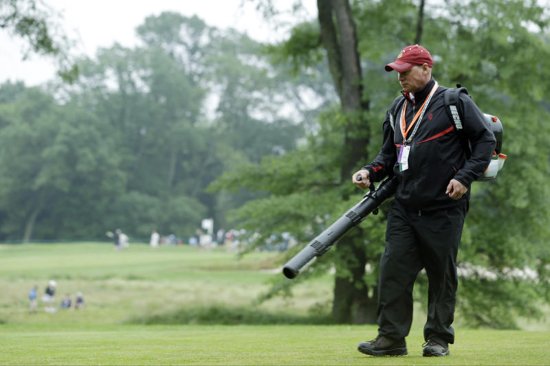 A course worker clears debris from the second hole after a weather delay during the first round of the U.S. Open golf tournament at Merion Golf Club, Thursday, June 13, 2013, in Ardmore, Pa. (AP Photo/Julio Cortez)