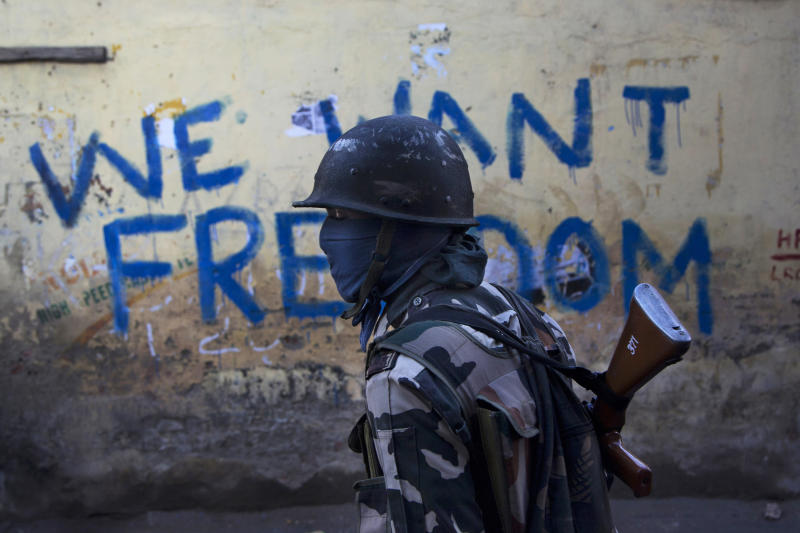 "FILE- In this Aug. 29, 2016 file photo, an Indian paramilitary soldier walks past graffiti on a wall in Srinagar, Indian-controlled Kashmir. As India considers its response to the suicide car bombing of a paramilitary convoy in Kashmir that killed dozens of soldiers on Feb. 14, 2019, a retired military commander who oversaw a much-lauded military strike against neighboring Pakistan in 2016 has urged caution. India blamed the attack on Pakistan and promised a ""crushing response."" New Delhi accuses its archrival of supporting rebels in Kashmir, a charge that Islamabad denies. (AP Photo/Dar Yasin, File)"