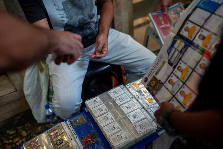 Traders and collectors meet to buy and exchange Panini World Cup football album stickers in front of a department store in downtown Rio de Janeiro