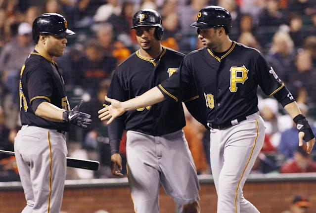 Pittsburgh Pirates' Neil Walker, right, and Jose Tabata, center, score and are greeted by Russell Martin during the fifth inning of an MLB National League baseball game against the San Francisco Giants in San Francisco, Thursday, Aug. 22, 2013. Walker and Tabata scored on an Alvarez double. (AP Photo/George Nikitin)