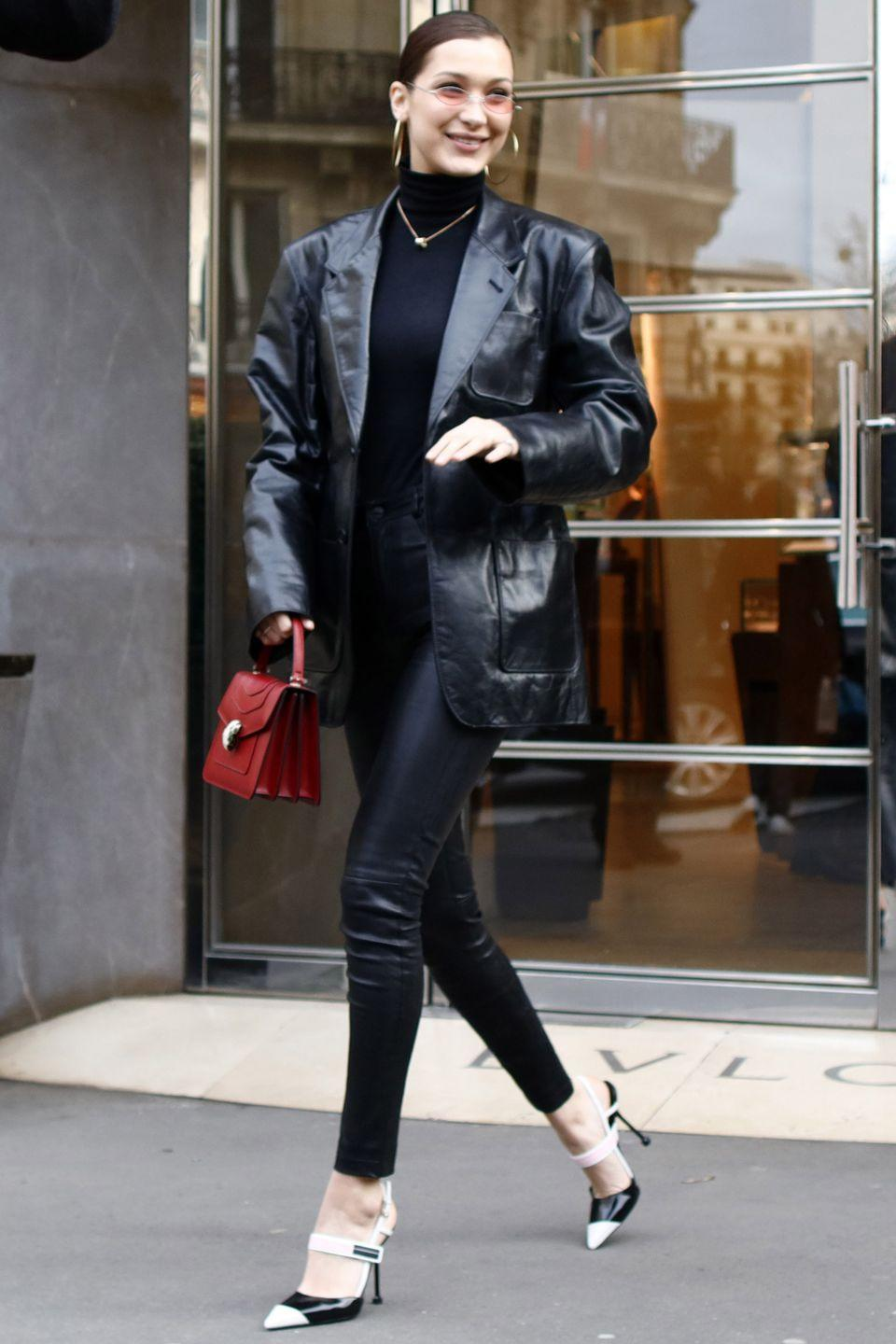 <p>In a black patent leather blazer over a turtleneck, with leather pants, a red mini purse, white and black stilettos, and small rose-tinted sunglasses while out in Paris.</p>