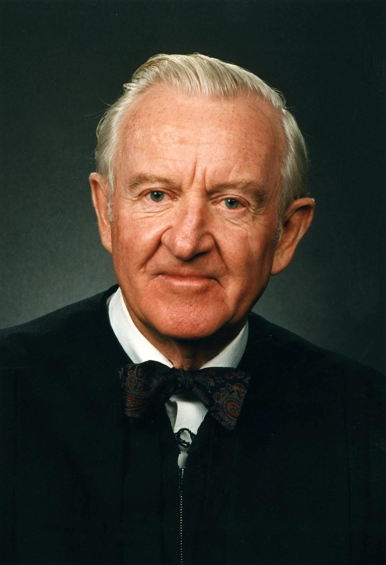 An official portrait of Justice John Paul Stevens in his judicialrobes and trademark bowtie.
