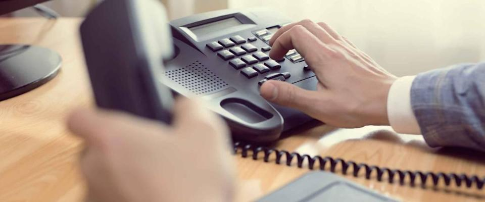 close up of man's hands dialing phone