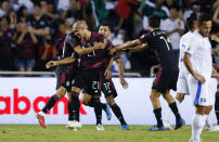 Mexico defender Luis Rodriguez (21) is congratulated by teammates after scoring a goal during a CONCACAF Group A soccer match against El Salvador, Sunday, July 18, 2021, in Dallas. (AP Photo/Brandon Wade)