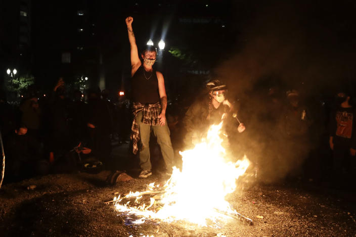 Demonstrators rally around a fire during a Black Lives Matter protest at the Mark O. Hatfield United States Courthouse Saturday, July 25, 2020, in Portland, Ore. (AP Photo/Marcio Jose Sanchez)