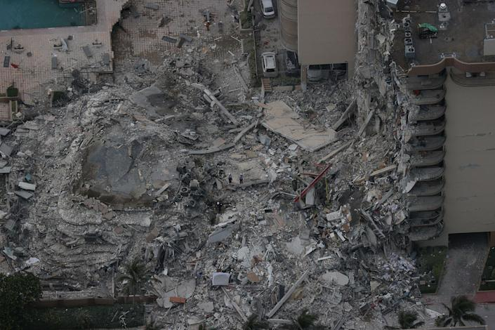 """Search and rescue personnel work in the rubble of the 12-story condo tower that crumbled to the ground in Surfside on June 24, 2021.<span class=""""copyright"""">Joe Raedle—Getty Images</span>"""