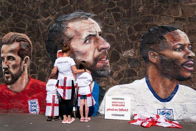 Fans by a new mural in Nuneaton by artist Nathan Parker, depicting Gareth Southgate, Harry Kane and Raheem Sterling