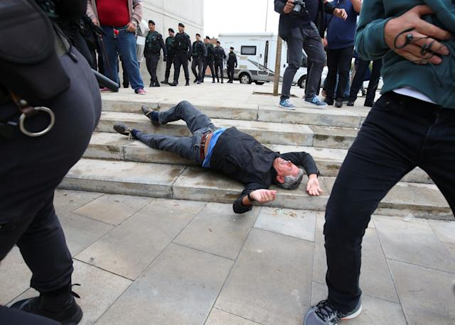 <p>A man falls to the ground during scuffles with Spanish Civil Guard officers outside a polling station for the banned independence referendum in Sant Julia de Ramis, Spain, Oct. 1, 2017. (Photo: Albert Gea/Reuters) </p>