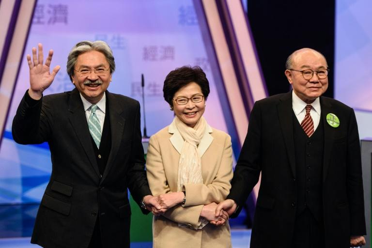 Hong Kong's three leadership candidates (L-R) John Tsang, Carrie Lam and ex-judge Woo Kwok-hing join hands in a Hong Kong TV studio before facing off in their first televised debate on March 14, 2017