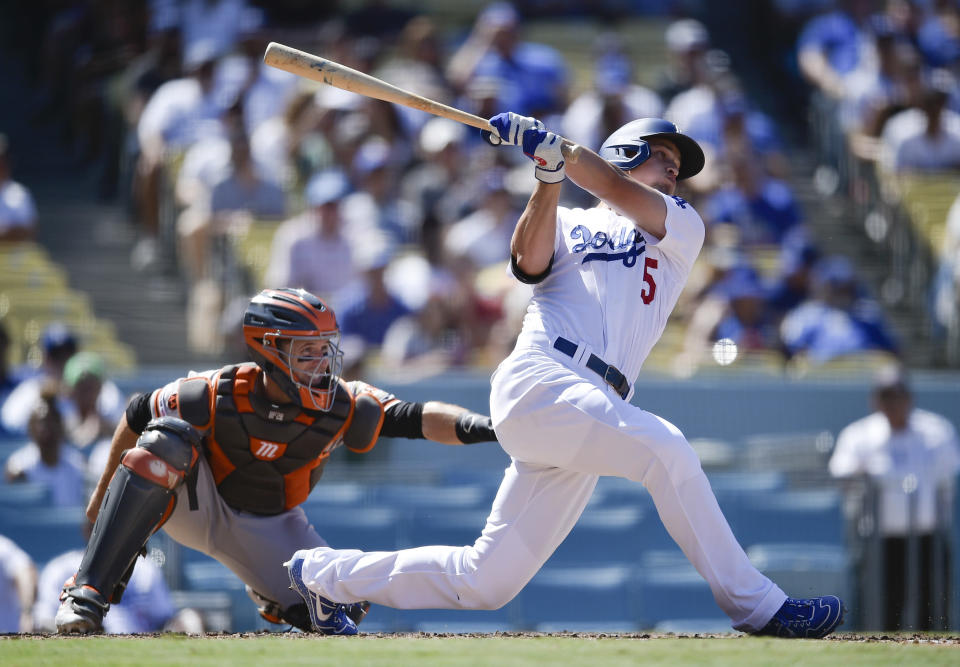 Los Angeles Dodgers' Corey Seager, right, follows through on a swing for a three-run home run during the fifth inning of a baseball game against the San Francisco Giants in Los Angeles, Sunday, Sept. 8, 2019. (AP Photo/Kelvin Kuo)