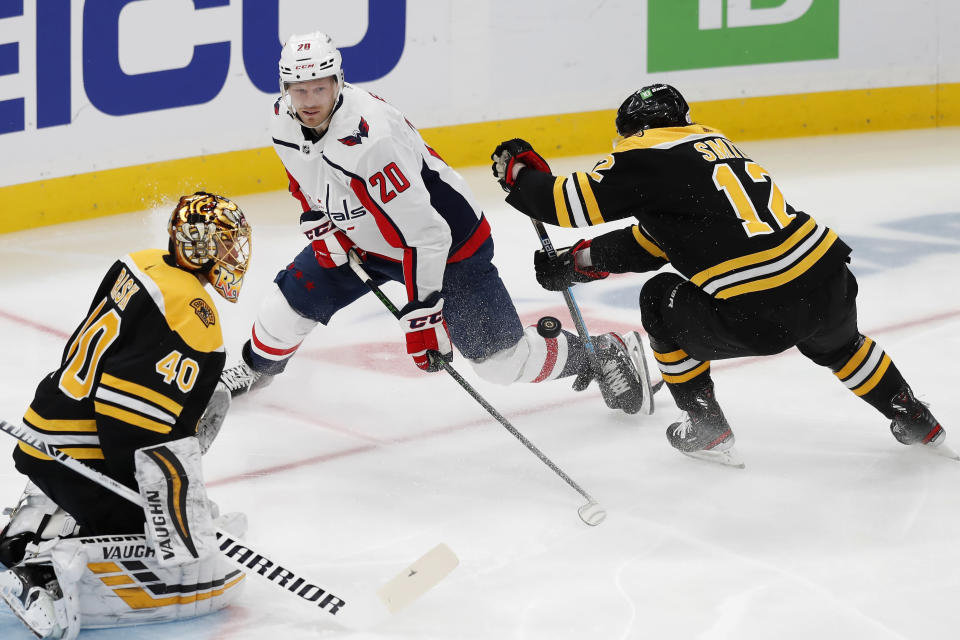 Boston Bruins' Craig Smith (12) defends against Washington Capitals' Lars Eller (20) during the first period of an NHL hockey game, Sunday, April 18, 2021, in Boston. (AP Photo/Michael Dwyer)
