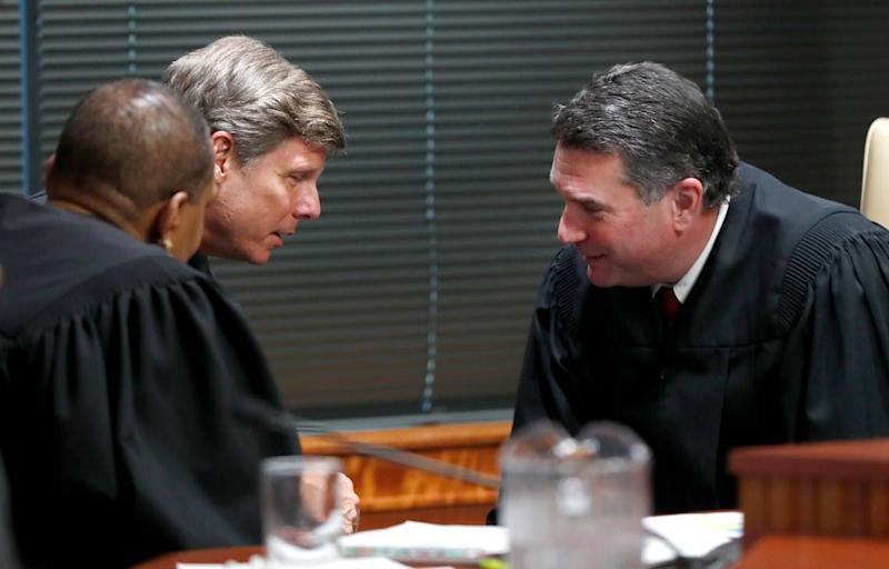 Judges Alma Hinton, left, Paul Ridgeway and Joseph Crosswhite confer during the first day of the gerrymandering trial challenging the North Carolina legislature district lines Monday, July 15, 2019. The trial is being held at Campbell University's Law School in Raleigh, N.C.