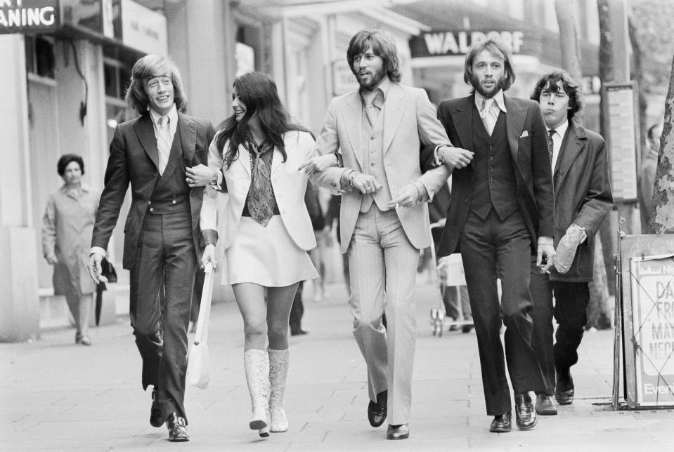 Recently re-formed pop group the Bee Gees, walking arm-in-arm with Linda Gray, London, 21st August 1970. Left to right: Robin Gibb (1949 - 2012), Linda Gray, Barry Gibb and Maurice Gibb (1949 - 2003). Gray and Barry Gibb were married the following month. (Photo by Jack Kay/Daily Express/Hulton Archive/Getty Images)