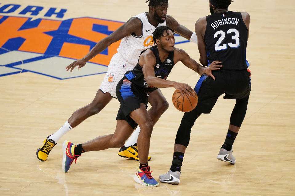 New York Knicks guard Immanuel Quickley (5) drives past Orlando Magic forward James Ennis III, left and teammate Knicks center Mitchell Robinson (23) during the first half of an NBA basketball game, Monday, Jan. 18, 2021, in New York. (AP Photo/Kathy Willens, Pool)