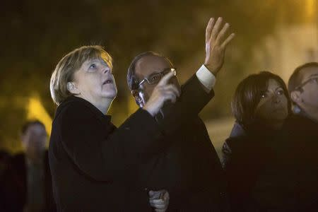 From L-R, German Chancellor Angela Merkel, French President Francois Hollande and Paris Mayor Anne Hidalgo each hold a white rose as they pay their respects to the victims of the November 13th fatal attacks at the Place de la Republique in Paris