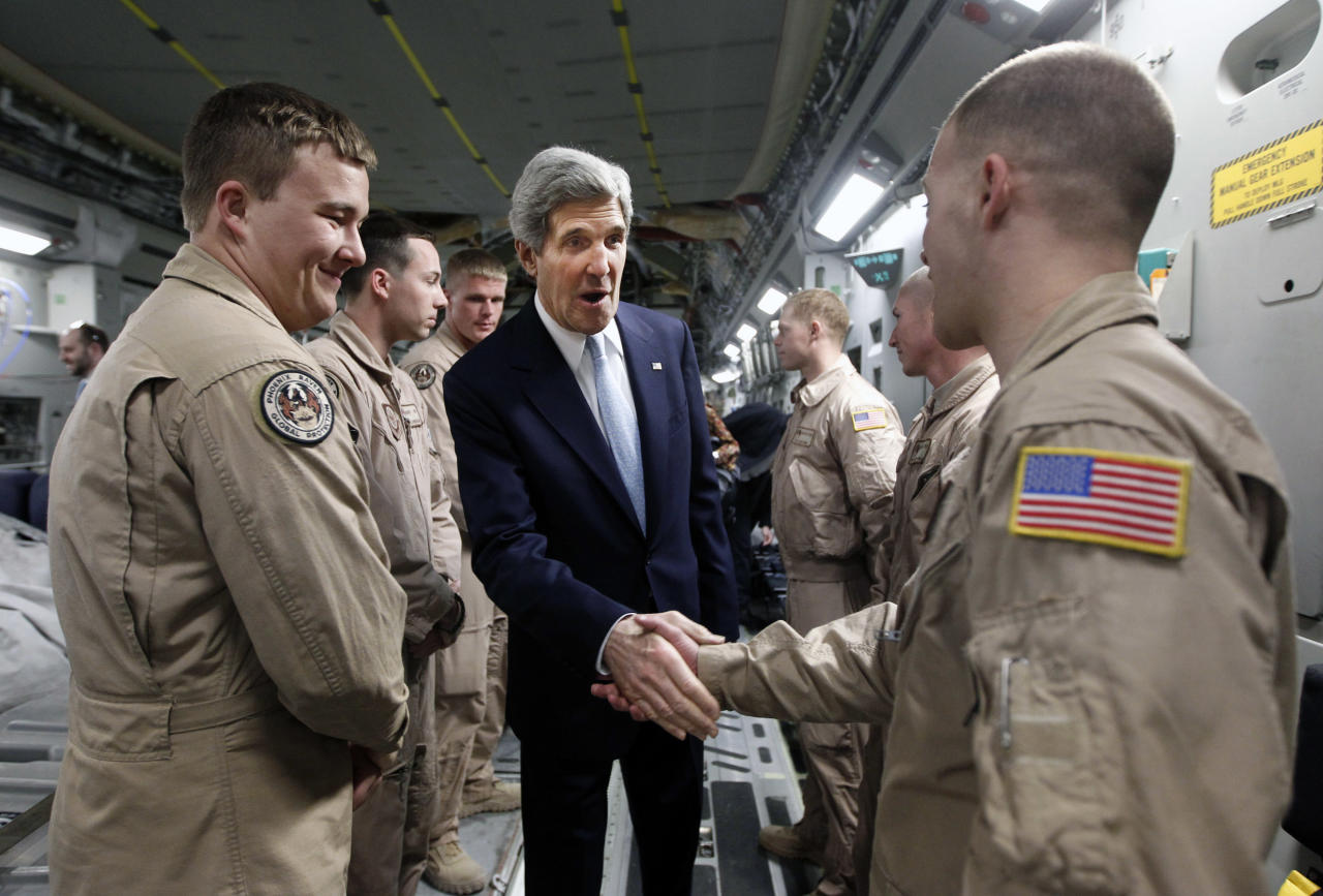 U.S. Secretary of State John Kerry, center, shakes hands with a member of the U.S. Air Force 816 Expeditionary Airlift Squadron aboard a C-17 aircraft en route to Baghdad from Amman, Sunday, March 24, 2013. (AP Photo/Jason Reed, Pool)