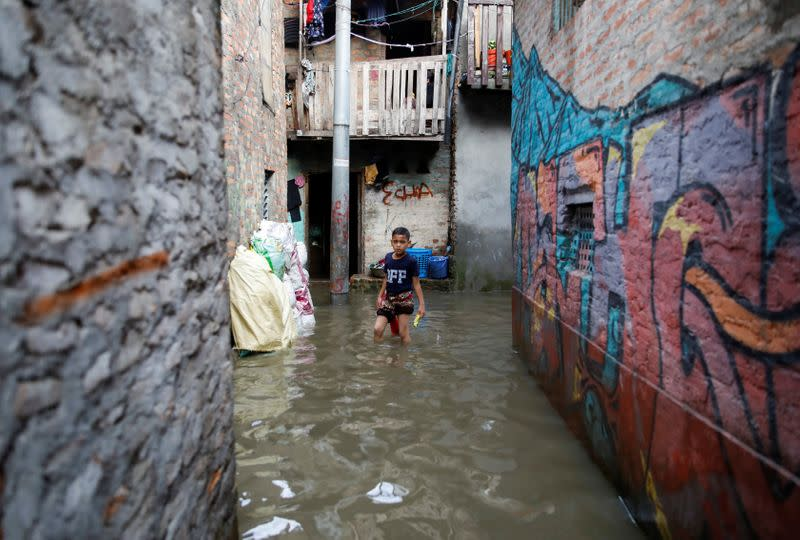 A boy walks along an alley as the river overflows due to incessant rainfall at a slum along the bank of Bagmati River in Kathmandu