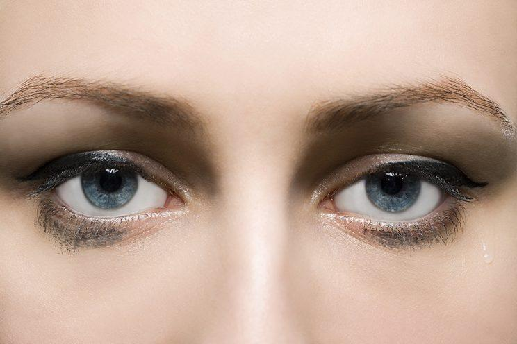 A woman's permanent makeup is running, giving her the appearance of having perpetually smudged eyeliner. (Photo: Getty Images)
