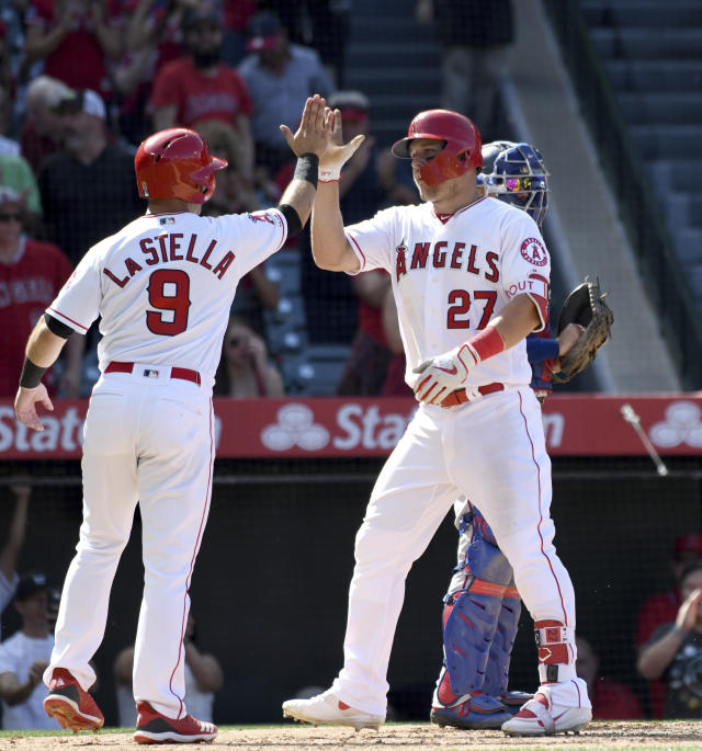 Los Angeles Angels' Mike Trout (27) is congratulated by Tommy La Stella (9) at home plate after scoring La Stella on a two-run home run during the sixth inning against the Texas Rangers in a baseball game Sunday, April 7, 2019, in Anaheim, Calif. (AP Photo/Michael Owen Baker)
