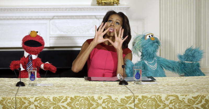 First lady Michelle Obama, center, with PBS Sesame Street's characters Elmo, left, and Rosita, right, to help promote fresh fruit and vegetable consumption to kids in an event in the State Dining Room of the White House in Washington, Wednesday, Oct. 30, 2013. Sesame Workshop and the Produce Marketing Association (PMA) joined in Partnership for a Healthier America (PHA) in announcing a 2-year agreement to making healthy choices by using the Sesame Street characters to help deliver the messages about fresh fruits and vegetables. (AP Photo/Pablo Martinez Monsivais)
