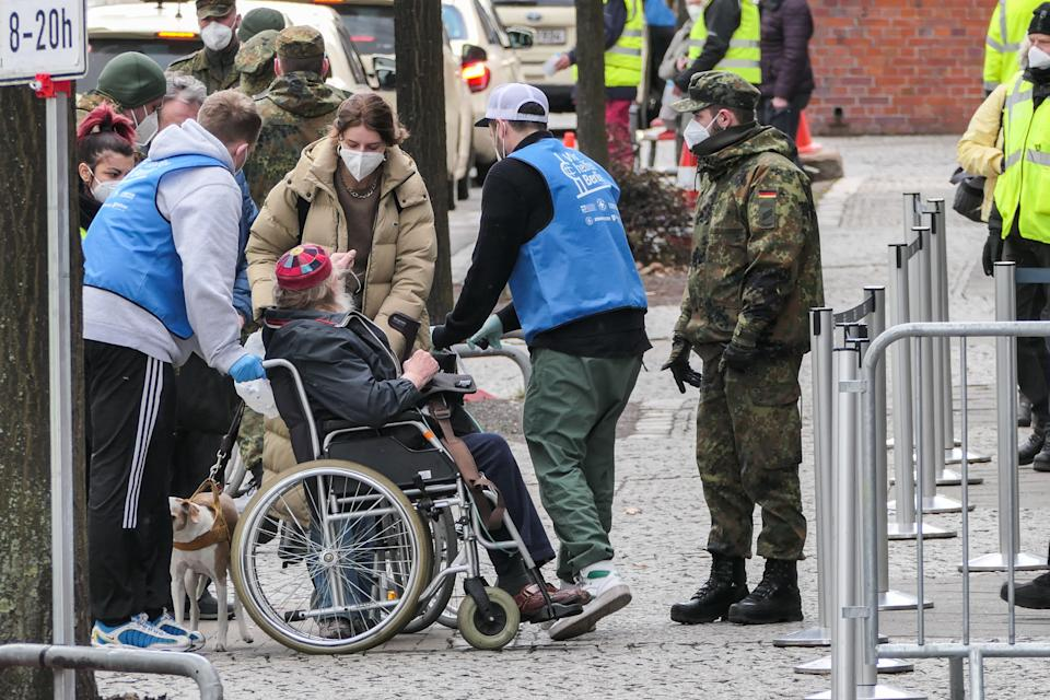 BERLIN, March 19, 2021 -- Staff members help an old man on a wheel chair enter a COVID-19 vaccination site in Berlin, capital of Germany, March 19, 2021. Germany's reported daily COVID-19 infections continued to rise sharply on Friday as the country registered 17,482 new cases in one day, the Robert Koch Institute RKI said on Friday. (Photo by Stefan Zeitz/Xinhua via Getty) (Xinhua/Stefan Zeitz via Getty Images)