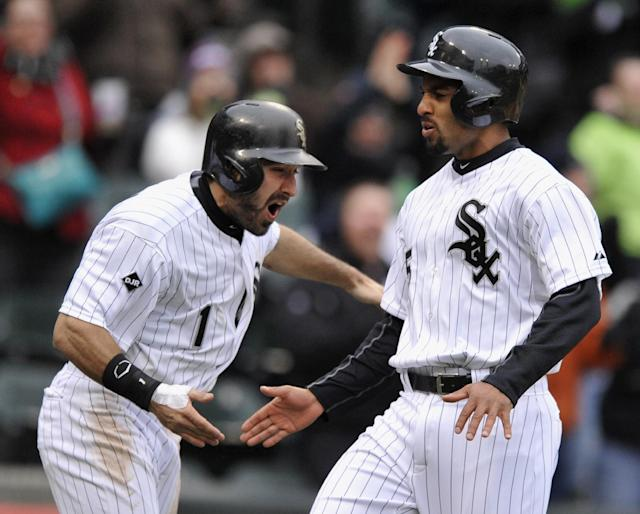 Chicago White Sox's Adam Eaton (1) celebrates with teammate Marcus Semien, right, after both scored on a Jose Abreu three-RBI triple during the six inning of an baseball game against the Minnesota Twins in Chicago, Thursday, April 3, 2014. (AP Photo/Paul Beaty)