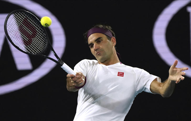 Switzerland's Roger Federer makes a forehand return to Hungary's Marton Fucsovics during their fourth round singles match at the Australian Open tennis championship in Melbourne, Australia, Sunday, Jan. 26, 2020. (AP Photo/Lee Jin-man)