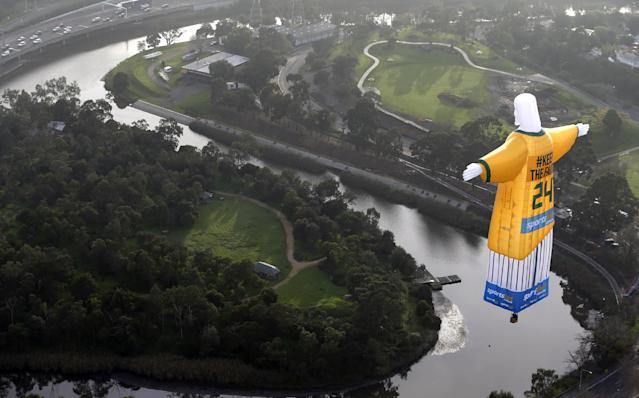 In this photo provided sportsbet.com.au, a hot air balloon in the likeness of Brazil's Christ The Redeemer statute, wearing the colors of Australia's soccer team floats over the Melbourne skyline Tuesday, June 10, 2014. Australia will begin their 2014 soccer World Cup campaign with a match against Chile Saturday, in Cuiaba. (AP Photo/sportsbet.com.au, Dave Callow)