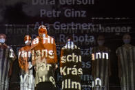 """Names of victims scroll on a mesh at the Jewish State Theatre as actresses perform wearing face masks for protection against COVID-19 infection, during the rehearsals for premiere of the """"The Beautiful Days of My Youth"""" play, based on the diary of Romanian Jewish Holocaust survivor Ana Novac, in Bucharest, Thursday, Oct. 15, 2020. Maia Morgenstern, second from left, head of the Jewish State Theater and a Romanian Jewish actress best known for playing Mary in Mel Gibson's controversial 2004 movie """"The Passion of the Christ,"""" described the play's staging in an interview with The Associated Press as an """"all-feminine project."""" (AP Photo/Andreea Alexandru)"""