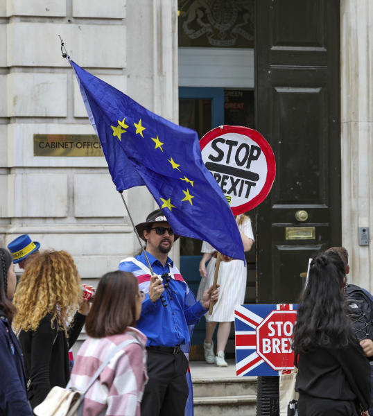 Anti-Brexit protesters demonstrate outside the Cabinet Office in Whitehall in London on Thursday, Aug. 15, 2019.  Demonstrations for both sides of the Brexit debate continue around parliament, as Prime Minister Boris Johnson has vowed that Britain will leave the EU on Oct. 31,  with or without a Brexit deal. (AP Photo/ Vudi Xhymshiti)