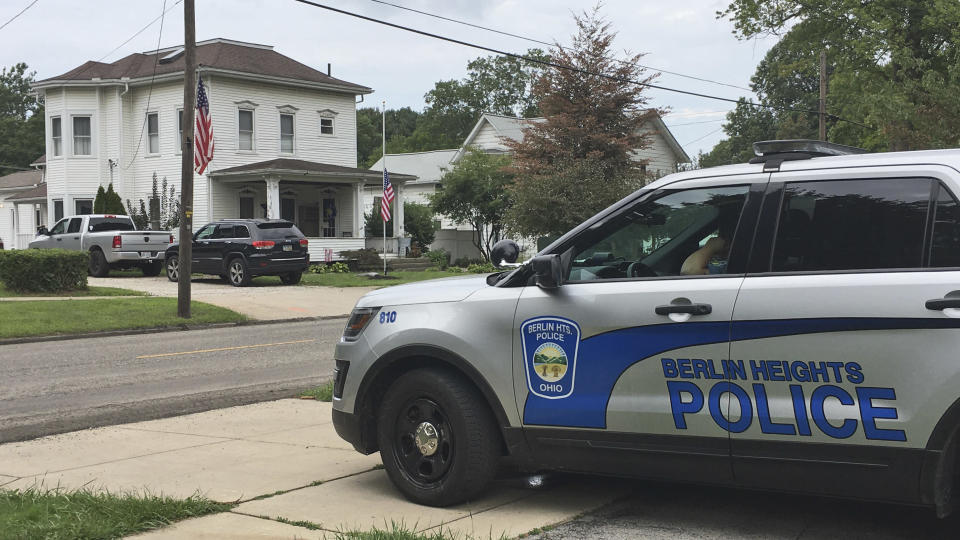 A Berlin Heights police officer sits across the road from the home of Maxton Soviak, Friday, August 27, 2021, in Berlin Heights, Ohio. Soviak, a U.S. Navy Fleet Marine Force hospital corpsman, was killed Thursday in Afghanistan. (AP Photo/John Seewer)
