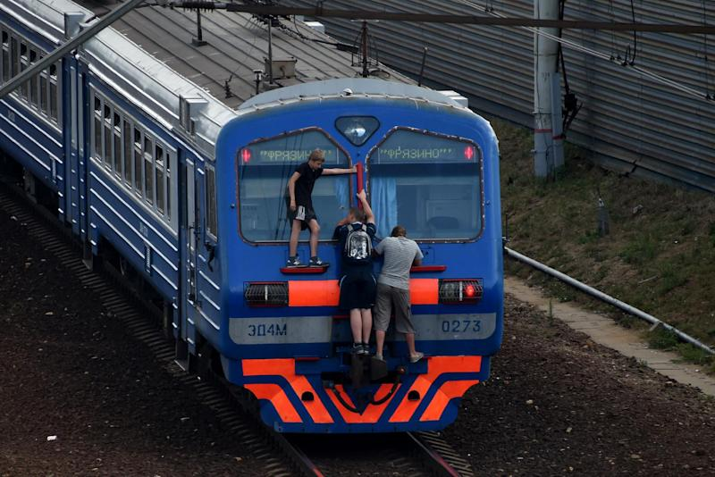 Men cling on a local train end on July 25, 2014 near the Losinoostrovskaya station in a suburb of Moscow (AFP Photo/Kirill Kudryavtsev)