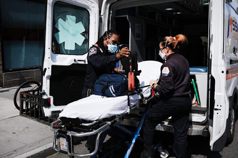 Ambulance workers clean a gurney at Mount Sinai Hospital on April 1 in New York City, where hospitals face shortages of beds, ventilators and protective equipment for medical staff.