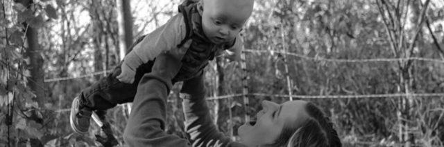 a mother playfully holding her son up in the air