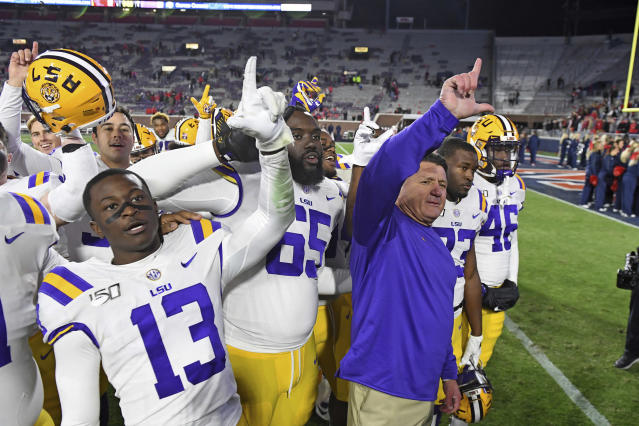 LSU coach Ed Orgeron and players celebrate after an NCAA college football game against Mississippi in Oxford, Miss., Saturday, Nov. 16, 2019. No. 1 LSU won 58-37. (AP Photo/Thomas Graning)
