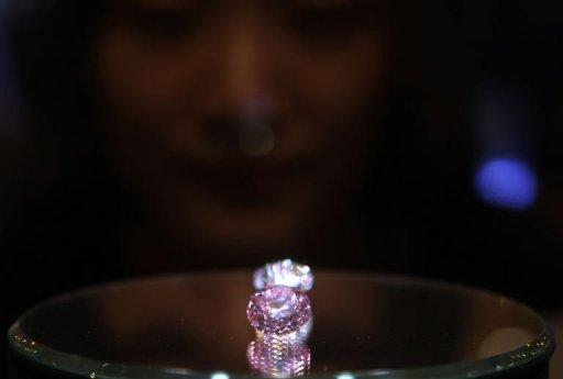 A woman looks at the 12.04 carat Martian Pink Diamond on display during a Christie's spring auction preview in Hong Kong on May 24, 2012. The diamond fetched $17.4 million at auction in Hong Kong this week as it went on sale for the first time in 36 years, more than double the estimated price
