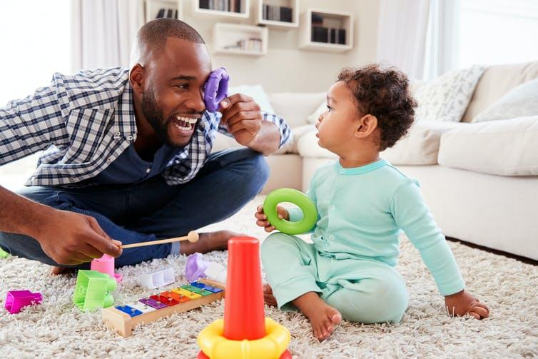 Man and toddler sat on floor playing with toys.