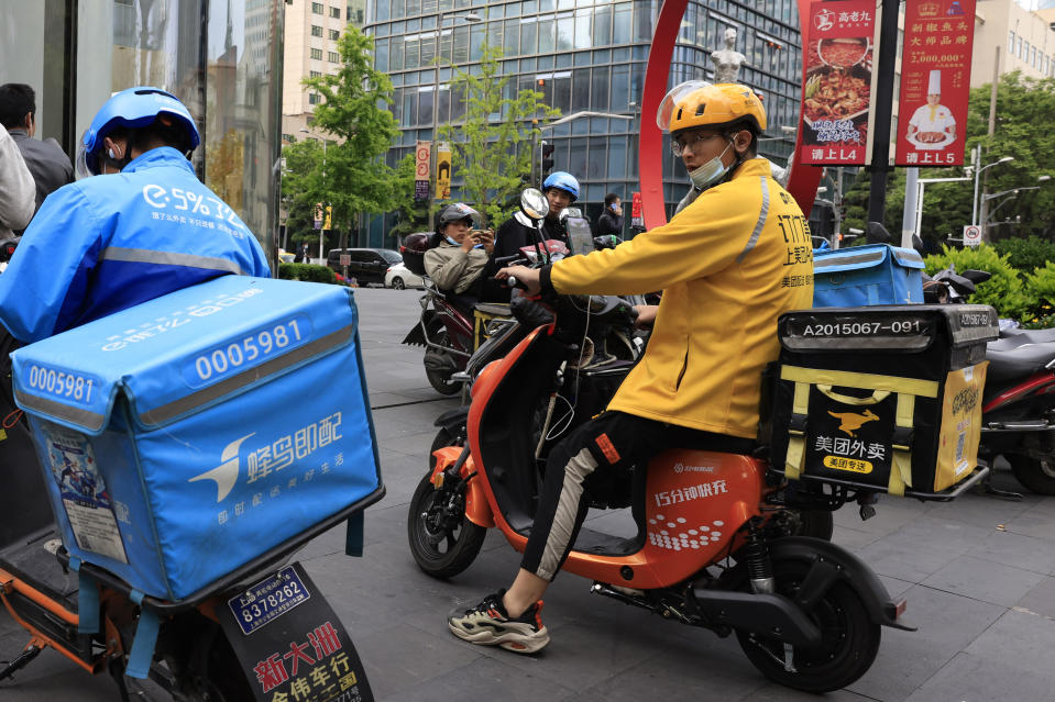 FILE - In this April 21, 2021, file photo, a Meituan delivery man in yellow goes on his rounds in Shanghai. Shares in Meituan, China's largest food delivery platform, have tumbled Tuesday, May 11, 2021 after its CEO posted -and then deleted - an ancient poem in a move widely seen as criticism of the Chinese government. Authorities are investigating the company over allegations of anti-monopolistic behavior, part of a wider crackdown on technology companies. (AP Photo/Ng Han Guan, File)