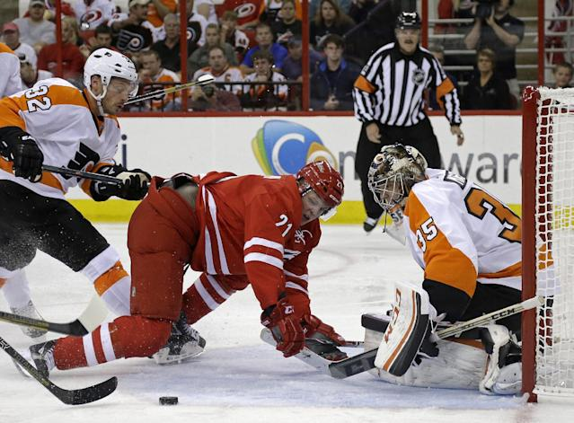 Philadelphia Flyers goalie Steve Mason (35) and Mark Streit (32) defend against Carolina Hurricanes' Drayson Bowman (21) during the second period of an NHL hockey game in Raleigh, N.C., Sunday, Oct. 6, 2013. (AP Photo/Gerry Broome)