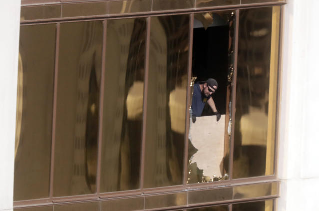 Agents from the FBI use binoculars from the broken window where Stephen Paddock opened fire at the Mandalay Bay Resort. (Photo: Gregory Bull)