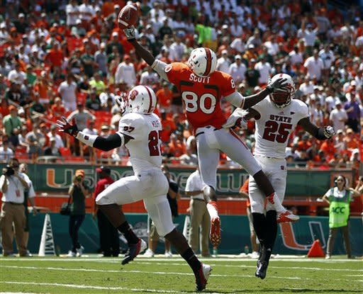 North Carolina State's Earl Wolff (27) and Dontae Johnson (25) pressure Miami's Rashawn Scott (80) as he reaches for a pass during the first half of an NCAA college football game in Miami, Saturday, Sept. 29, 2012. (AP Photo/J Pat Carter)