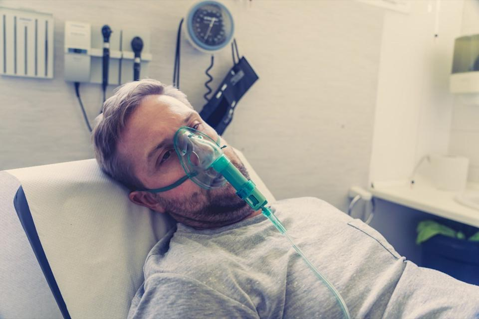 man with oxygen mask looking sad and worried at hospital bed in clinic bedroom