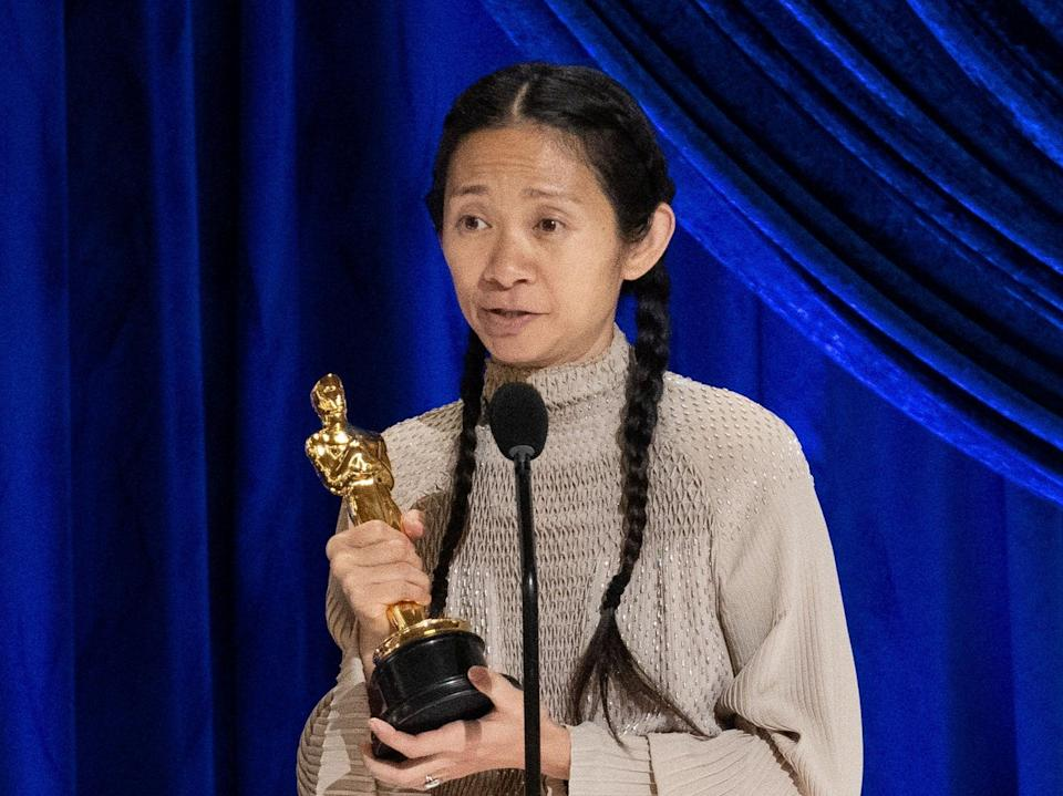 Chloe Zhao collecting the Best Director award (via REUTERS)