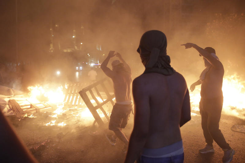 Anti-government protesters set fire to plastic barriers and trash to block a road during a demonstration in Beirut, Lebanon, Thursday, Oct. 17, 2019. Scores of people are protesting in Beirut and other parts of Lebanon over the government's plans to impose new taxes amid a harsh economic crisis in the country. (AP Photo/Hassan Ammar)