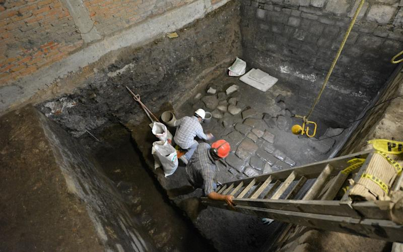 Archaeologists work on slabs of basalt belonging to vestiges of a pre-Hispanic palace -  INAH via REUTERS