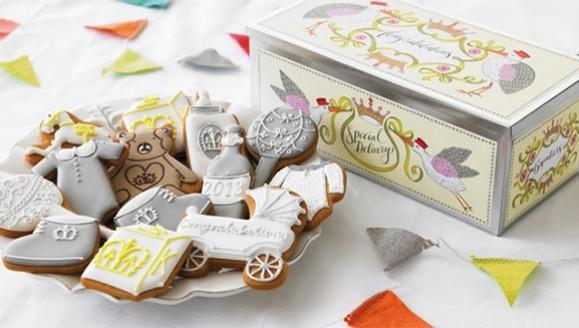 """The limited edition Royal Baby tin from London's Biscuiteers features, """"traditional silver spoons, regal rattles and the obligatory celebratory fizz,"""" according to the family-owned company's website."""